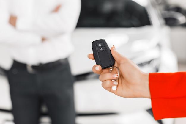 Zbliżenie samochodu klucz w żeńskiej ręce. .