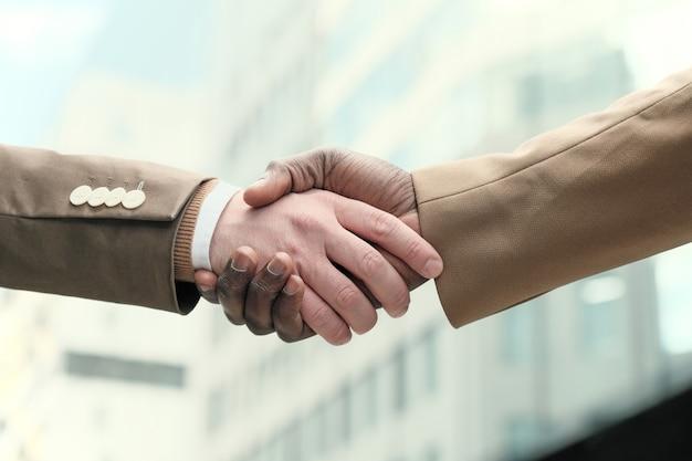 Zbliżenie: ściskanie rąk na zewnątrz ludzi biznesu