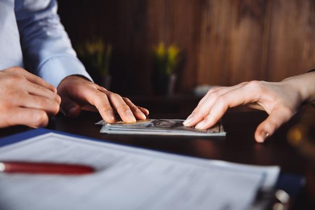 Zbliżenie: sędzia ręce liczenia banknotów przed młotkiem przy biurku