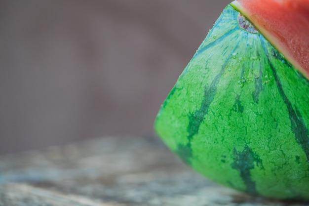 Zbliżenie selekcyjnej ostrości strzał pokrojeni arbuzów kawałki na popielatym drewnianym tle