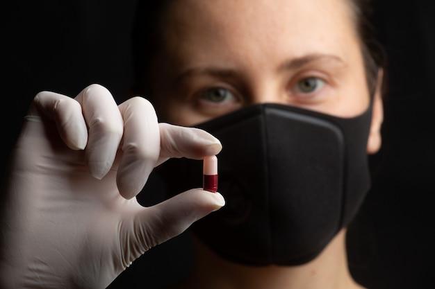 Zbliżenie, selektywne focus, dziewczyna w masce ochronnej trzyma w dłoni pigułkę. koncepcja leków. koronawirus (covid-19.