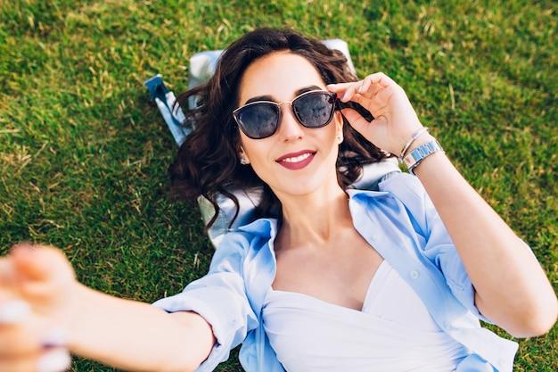 Zbliżenie selfie portret śliczna brunetka dziewczyna z krótkimi włosami na trawie w parku. nosi białą koszulkę i niebieską koszulę, okulary przeciwsłoneczne. widok z góry.