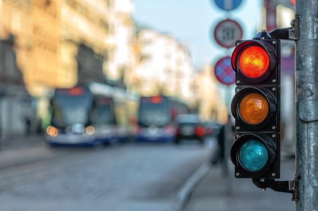 Zbliżenie semafora małego ruchu z czerwonym światłem na tle ruchu miejskiego