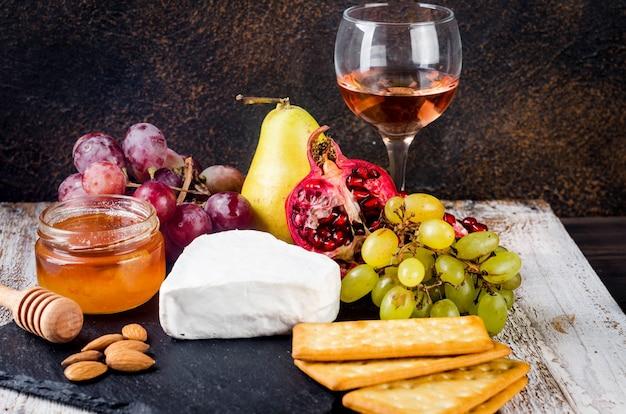 Zbliżenie sera camembert z miodem, orzechami, winoroślą. wykwintny talerz serów, jedzenie wina. camembert, bree. miękki francuski ser. włoskie jedzenie. nabiał.
