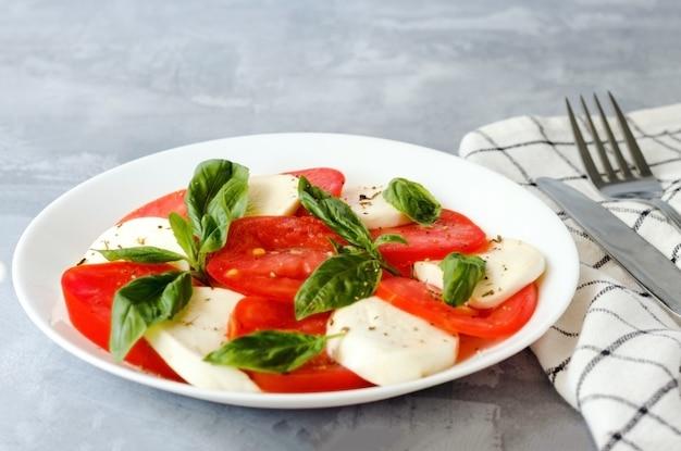 Zbliżenie sera i pomidorów z liśćmi bazylii w talerzu