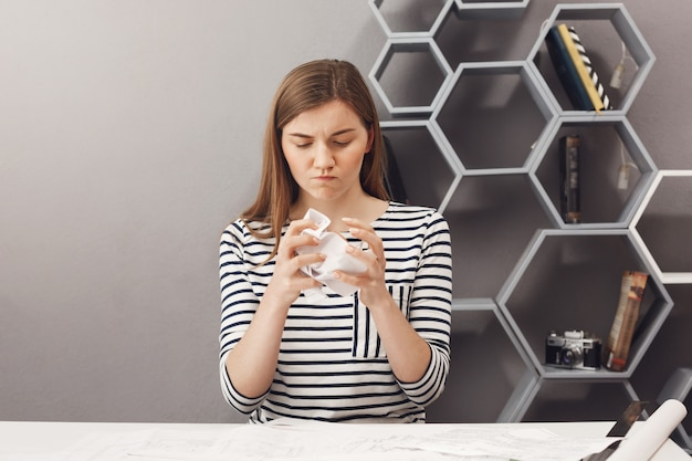 Zbliżenie sfrustrowanej pięknej europejskiej ciemnowłosy żeński niezależny projektant zgniata papier rękami i wyrazem twarzy, będąc zły, że nic nie działa.
