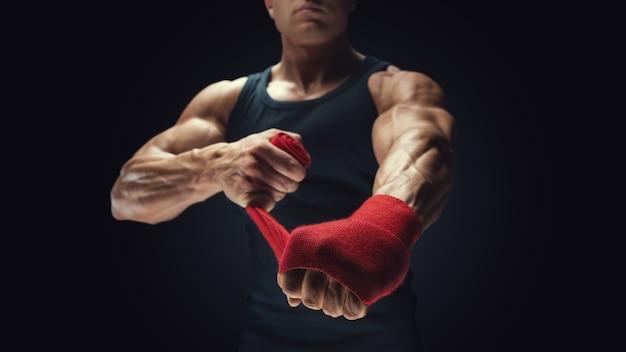 Zbliżenie: siłacz owija ręce na czarnym tle mężczyzna owija ręce czerwonymi okładami bokserskimi na czarnym tle silne dłonie i pięści, gotowe do treningu i aktywnego ćwiczenia