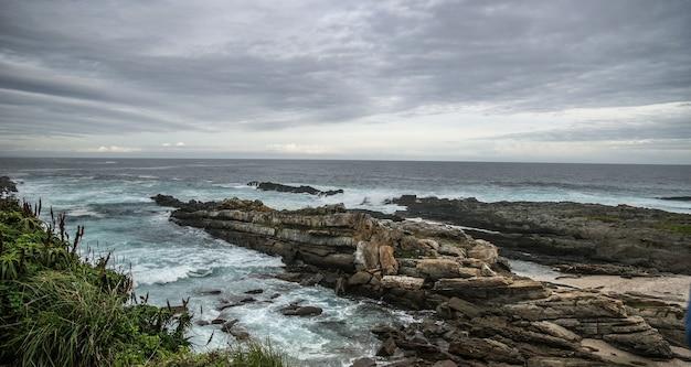 Zbliżenie skał na plaży pod niebem pełnym chmur