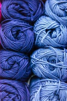 Zbliżenie skali niebieskich przędz wełnianych posortowanych według koloru i przechowywania na półce
