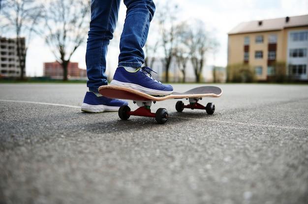 Zbliżenie skater nogi. dzieciak jeździ na deskorolce na zewnątrz