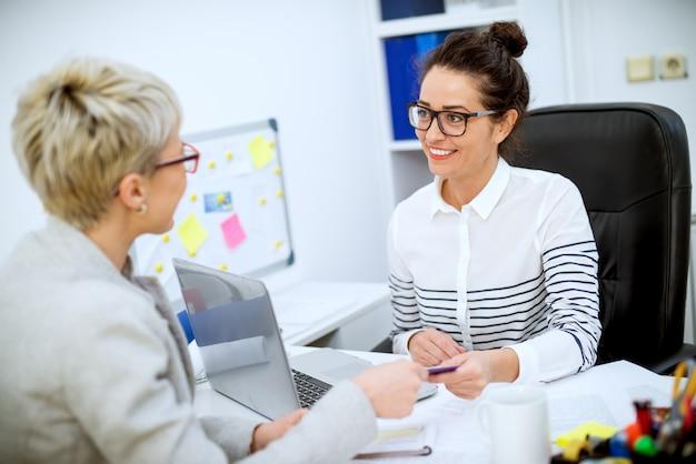 Zbliżenie skoncentrowany profesjonalny zadowolony pracownik kobieta, biorąc kartę bankową od klientki w biurze.