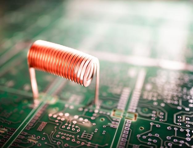 Zbliżenie skręcony drut miedziany stoi na zielonym mikroukładzie. koncepcja sprzętu komputerowego. fabryka do produkcji obwodów oscylacyjnych i urządzeń wysokiej częstotliwości