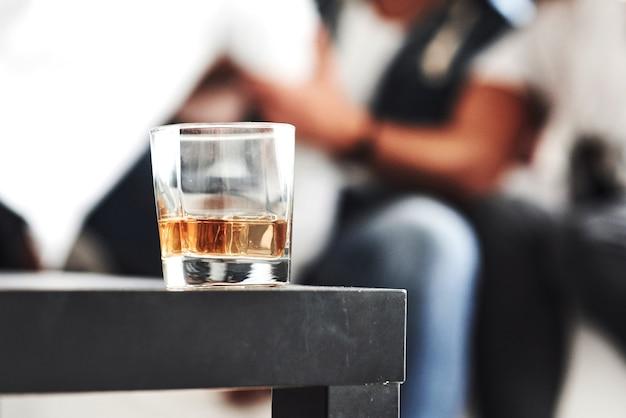 Zbliżenie skupione zdjęcie szkła z whisky stojącego na czarnym stole z zamazanymi ludźmi w tle
