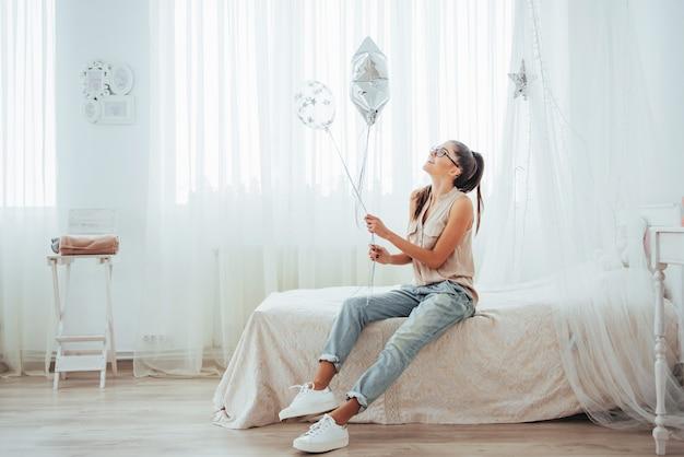 Zbliżenie śliczna brunetki dziewczyna uśmiecha się szeroko i bawić się z balonami przejrzystymi i srebnymi. nosi okulary i kręcone włosy.