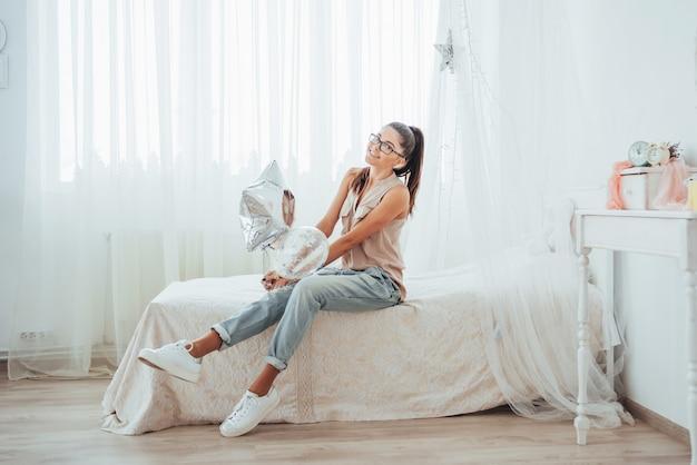 Zbliżenie śliczna brunetki dziewczyna uśmiecha się szeroko i bawić się z balonami przejrzystymi i srebnymi.