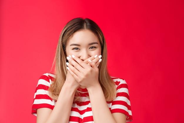 Zbliżenie śliczna delikatna głupia azjatycka dziewczyna chichocząca głupcem wokół zabawy naciśnij dłonie usta obiecują nie...