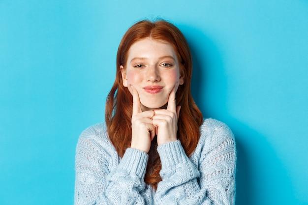 Zbliżenie: śliczna i głupia dziewczyna z czerwonymi włosami szturchającymi w policzki, pokazująca dołeczki i uśmiechnięta, stojąca na niebieskim tle.