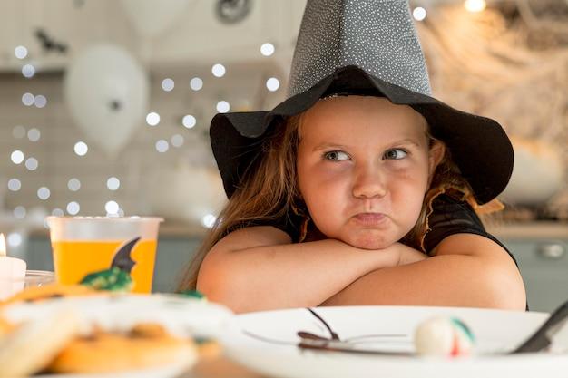 Zbliżenie: śliczna mała dziewczynka z kostiumem czarownicy