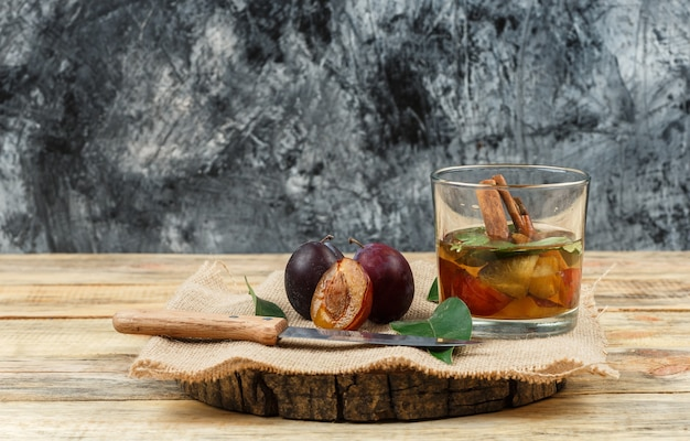 Zbliżenie śliwki i nóż na drewnianej desce z wodą detoksykacyjną, kawałek worek i liście na drewnianej desce i granatowej marmurowej powierzchni. poziomy