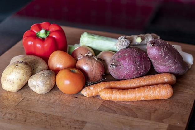 Zbliżenie słodkich ziemniaków, pomidorów, cebuli, marchewki, papryki, ziemniaków i imbiru na drewnianym stole