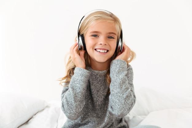 Zbliżenie słodkie uśmiechnięte dziewczyny w słuchawkach, siedząc na łóżku,