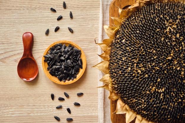 Zbliżenie słoneczników i nasion słonecznika w drewnianym półmisku i łyżką na rustykalnym stole z miejscem na kopię