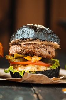 Zbliżenie smakowitego czarnego hamburgeru ciemny drewniany stół