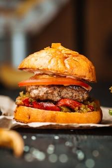 Zbliżenie smakowity hamburger na ciemnym drewnianym stole