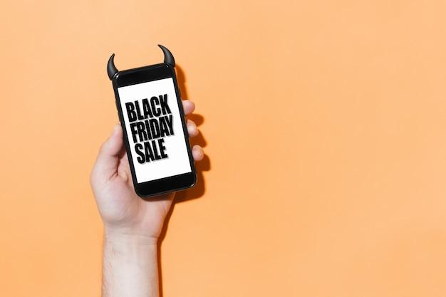 Zbliżenie smartfona ze sprzedażą w czarny piątek na ekranie, w przypadku z rogami diabła na tle koloru pomarańczowego.