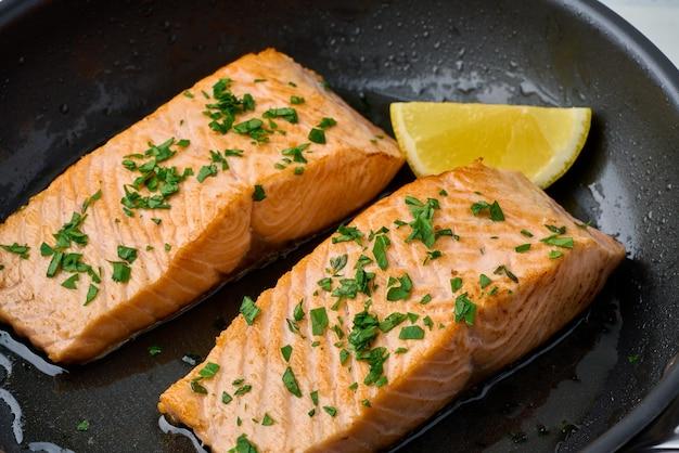 Zbliżenie smażony soczysty filet z łososia z pietruszką i cytryną na pan
