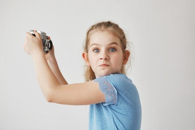 Zbliżenie śmieszne blondynka w niebieskiej koszuli, trzymając aparat w ręce, zamierza zrobić selfie, gdy jej przyjaciel zaczyna się z niej śmiać.