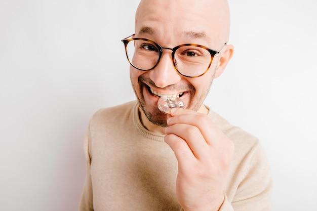 Zbliżenie śmieszne portret łysy mężczyzna. chciwy górnik kryptowaluty gryzie metalowe monety bitcoin, aby sprawdzić autentyczność.