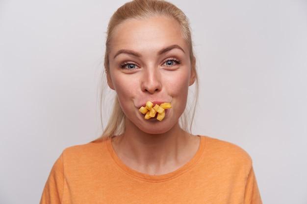 Zbliżenie śmiesznej atrakcyjnej młodej blondynki z przypadkową fryzurą, która patrzy radośnie na kamerę i ma usta pełne frytek, wygłupia się z jedzeniem, pozując na białym tle
