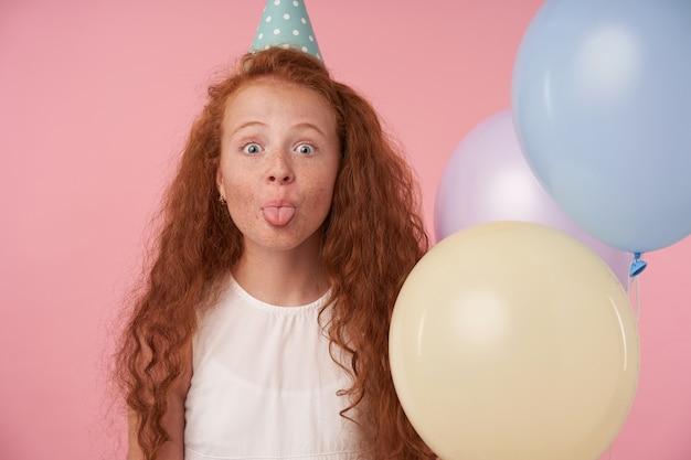 Zbliżenie śmiesznej rudowłosej dziewczyny z kręconymi włosami w białej sukni i czapce urodzinowej coś świętuje, radośnie patrząc w kamerę i pokazując język. pozowanie na różowym tle z kolorowymi balonami
