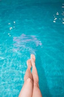 Zbliżenie smukłych kobiecych nóg na tle błękitnej wody przy basenie w upalny letni dzień, pod słońcem. dziewczyna macha nogami w wodzie basenu, odpoczywając, opalając się.