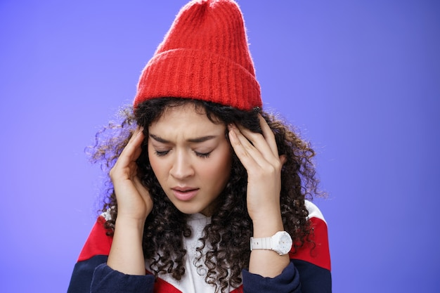 Zbliżenie smutna i chora śliczna stylowa kobieta w czerwonej ciepłej czapce zamyka oczy, pocierając skronie, czując zmęczenie i ból głowy, gdy łapie przeziębienie, stojąc ze straszną migreną nad niebieską ścianą.