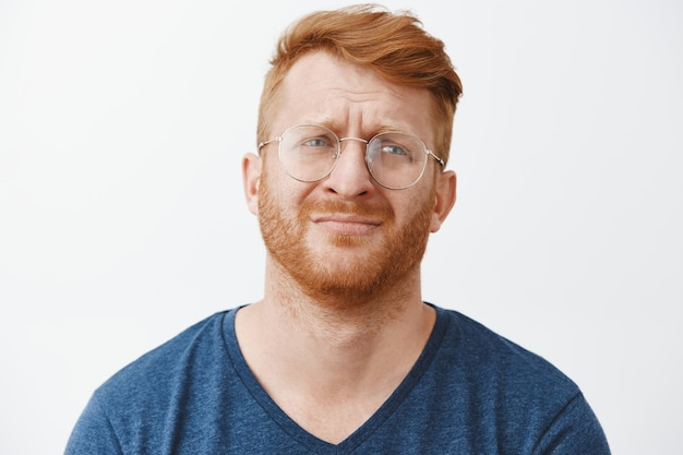 Zbliżenie: smutny i nieszczęśliwy, brodaty rudy mężczyzna w okularach jęczący, patrząc zdenerwowany