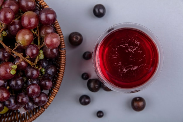 Zbliżenie soku z czarnych winogron w szkle z winogronami w koszu i na szarym tle
