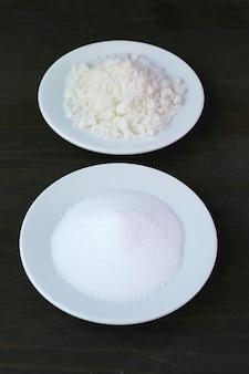 Zbliżenie soli kuchennej z rozmytą solą morską na czarnym tle