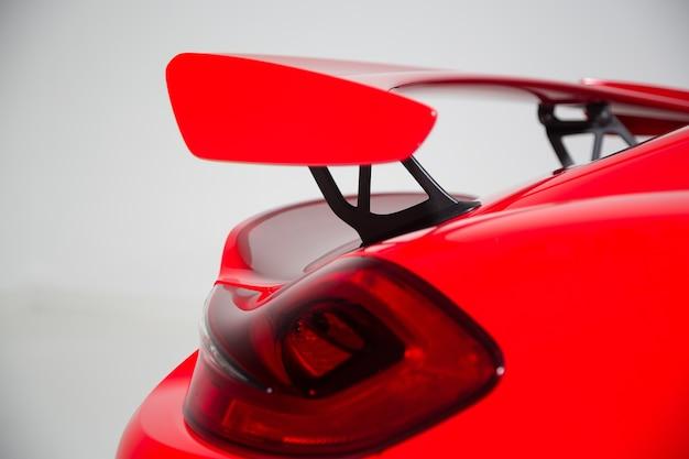 Zbliżenie spoiler na czerwony nowoczesny samochód sportowy pod światłami na białym tle