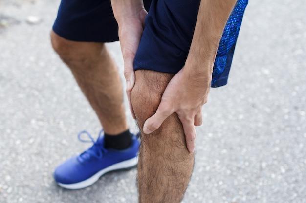 Zbliżenie sportowca cierpiącego z powodu bólu na sportowej kontuzji kolana po uruchomieniu.