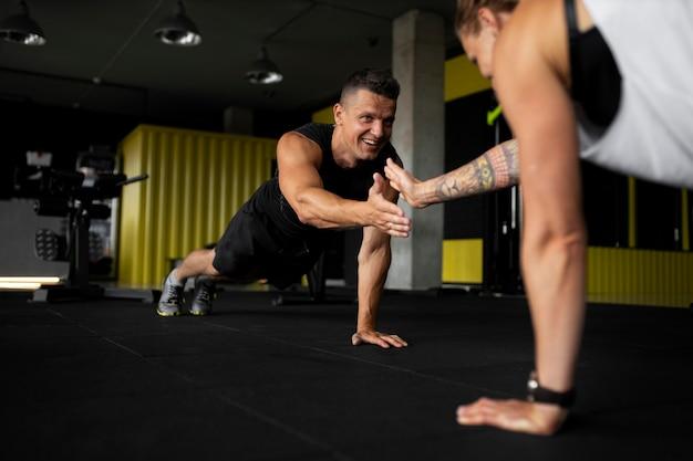 Zbliżenie sportowców trzymających się za ręce na siłowni