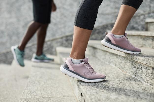 Zbliżenie sportowców w tenisówkach podbiegających po schodach podczas treningu na świeżym powietrzu