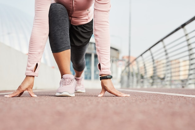 Zbliżenie: sportsmenka w stroju sportowym stojąca w pozie, biorąca udział w zawodach biegowych