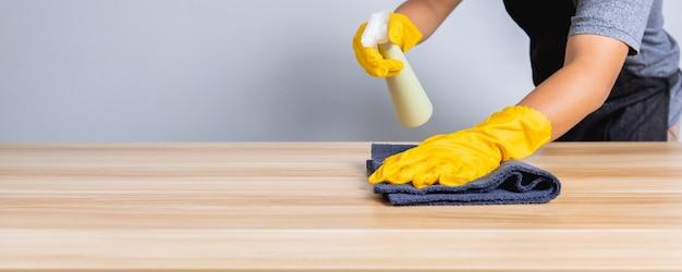 Zbliżenie: sprzątacz pracujący w sklepie czystym na drewnianym stole, koncepcja ochrony koronawirusa