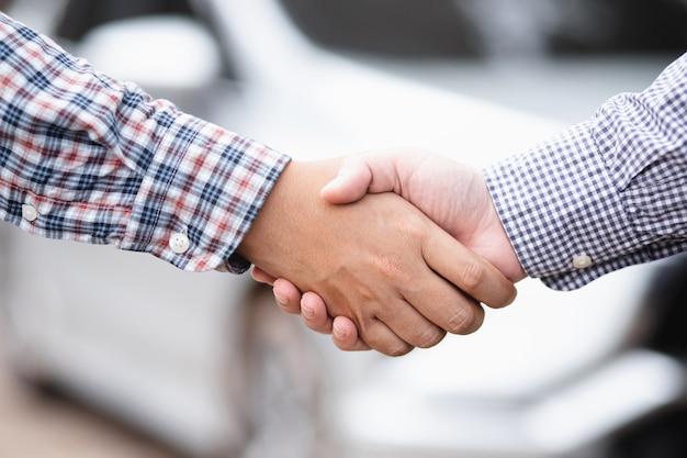 Zbliżenie sprzedawcy, podając klucz do nowego właściciela i uścisk dłoni w salonie samochodowym lub salonie