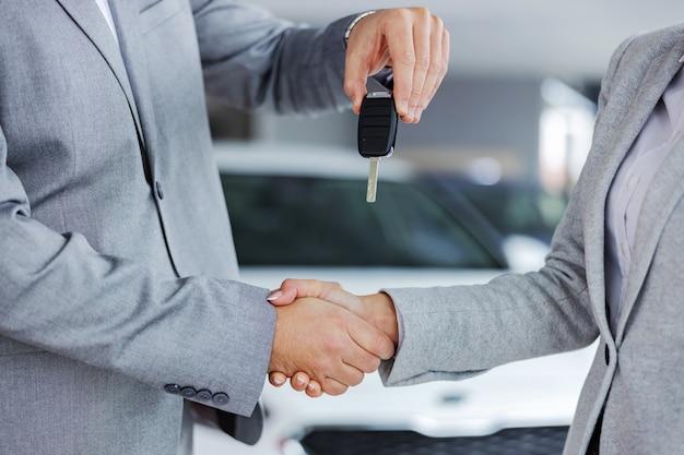 Zbliżenie sprzedawcy samochodów, ściskając ręce z klientem i wręczając jej kluczyki do samochodu, stojąc w salonie samochodowym