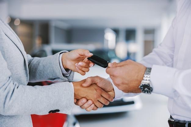 Zbliżenie sprzedawcy samochodów stojących w salonie samochodowym