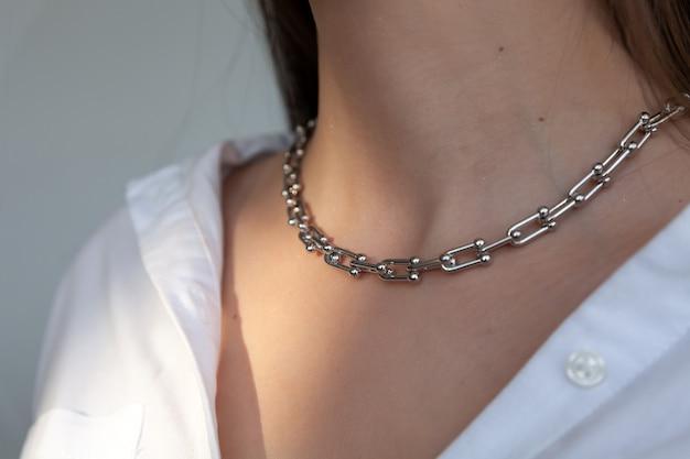 Zbliżenie srebrny łańcuszek na kaukaski kobieta model brunetka z długimi włosami, metalowy naszyjnik
