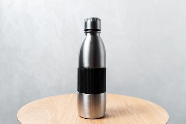 Zbliżenie: stalowa butelka termiczna wielokrotnego użytku na drewnianym stole przeciwko szarej ścianie.